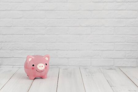 Pink piggy bank on white wood table over white brick background with copy space.