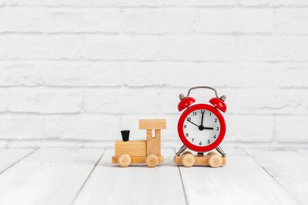 Red alarm clock on wood train over white background with copy space Фото со стока - 130126931