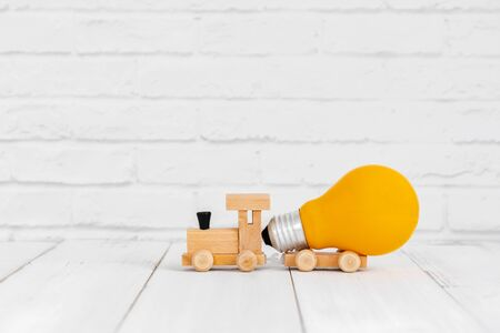 Yellow light bulb on wood train over white background with copy space