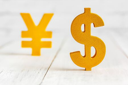Dollar sign over yen sign on white wood table over white brick background with copy space.