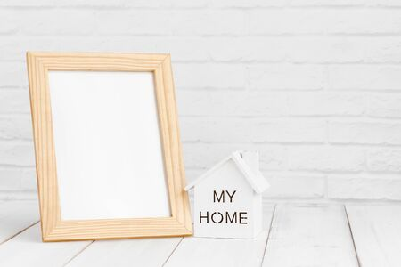 Photo frame and home shaped on white wood table with copy sapce.