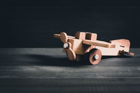 Wooden toy plane on wood table background.
