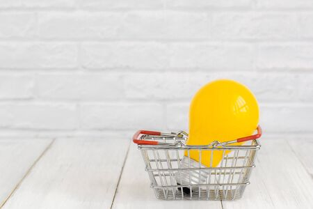 Yellow light bulb with basket on white wood table over white brick background with copy space.