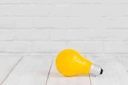 Yellow light bulb on white wood table over white brick background with copy space.