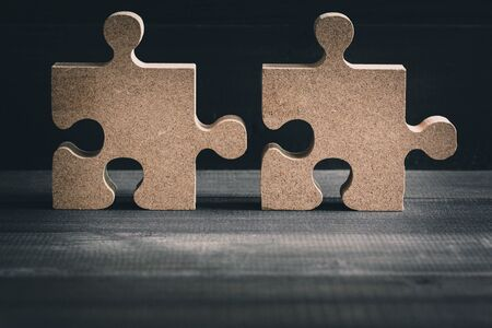 Wooden jigsaw puzzle on wood table background. Business solving , Teamwork and partnership concept