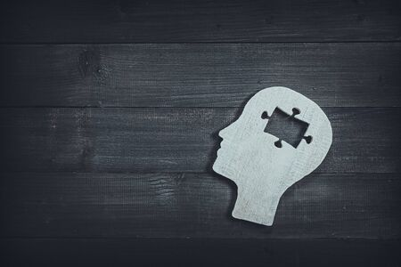 Human head and face with puzzle sign on wood table background. Brain of thinking about connection , Symbol of Process and Positive Mind concept