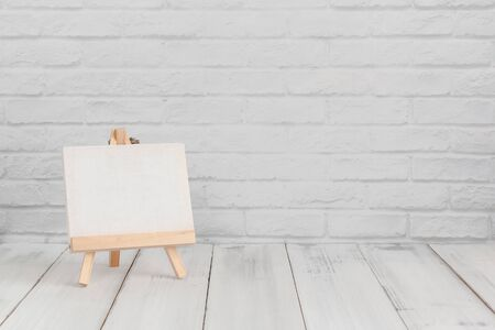 Empty drawing canvas on white wood table over white brick background with copy space.
