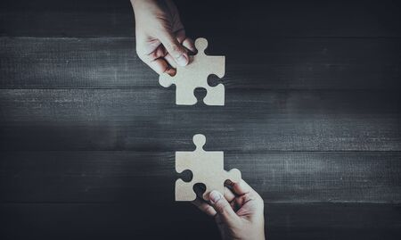 Two hands holding wooden jigsaw puzzle pieces and solving put pieces of the puzzle together. Business solving , Teamwork and partnership concept