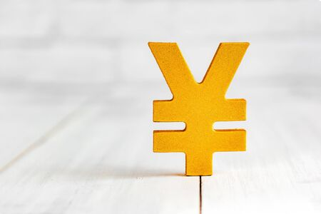 Golden yen sign on white wood table over white brick background with copy space.