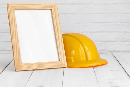 Photo frame and safety hat on white wood table with copy sapce, building concept.