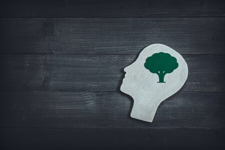 Human head and face with green tree sign on wood table background. Brain of thinking about green nature , Symbol of Process and Positive Mind concept Zdjęcie Seryjne