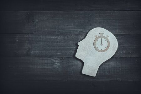 Human head and face with timer watch  sign  on wood table background. Brain of thinking about time management , Symbol of Process and Positive Mind concept