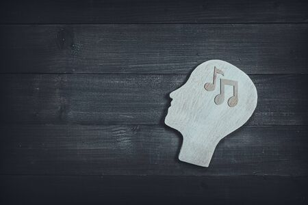 Human head and face with music note sign on wood table background. Brain of thinking about music , Symbol of Process and Positive Mind concept