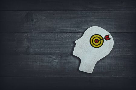 Human head and face with dartboard  sign  on wood table background. Brain of thinking about target and strategy , Symbol of Process and Positive Mind concept
