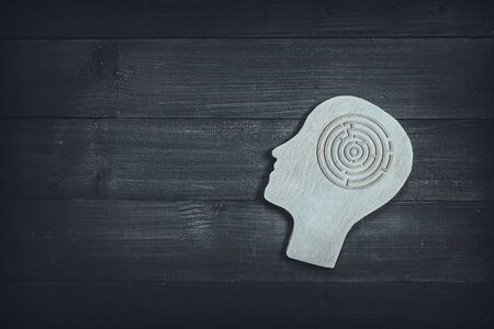 Human head and face with circle maze sign on wood table background. Brain of thinking about solving problem , Symbol of Process and Positive Mind concept
