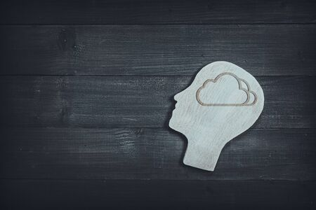 Human head and face with cloud sign  on wood table background. Brain of thinking about dream , Symbol of Process and Positive Mind concept