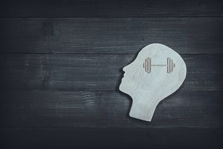 Human head and face with barbell sign on wood table background. Brain of thinking about health , Symbol of Process and Positive Mind concept