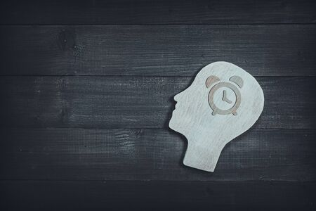 Human head and face with alarm clock  sign  on wood table background. Brain of thinking about time management , Symbol of Process and Positive Mind concept