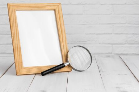 Photo frame and magnifying on white wood table with copy sapce, research concept.