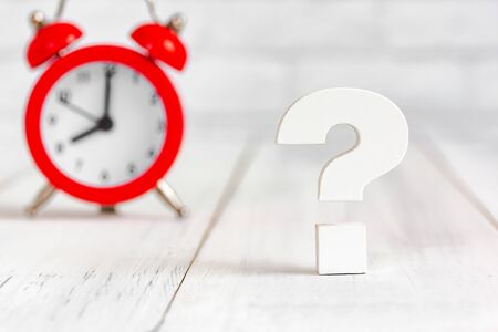 Question mark with alram clock on white wood table over white brick background with copy space.
