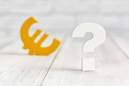 Question mark with euro sign on white wood table over white brick background with copy space.
