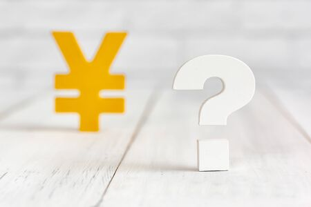 Question mark with yen sign on white wood table over white brick background with copy space.