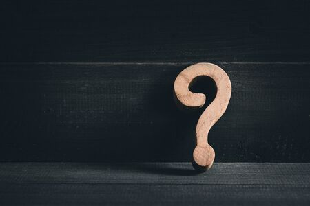 Wooden question mark on wood table background. Problem solving concept.