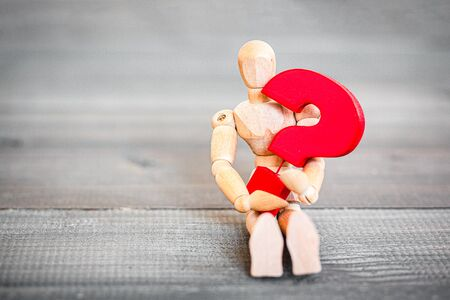 Jointed Wooden Doll hugging red question mark