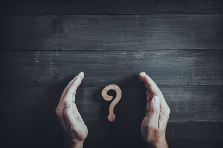 Hands protect wooden question mark on wood table background.  Problem solving concept.