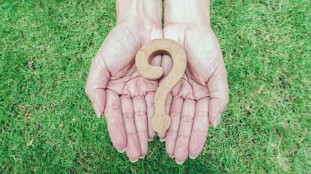 Wooden question marsk on woman hands over green grass background. Ploblem solving concept.