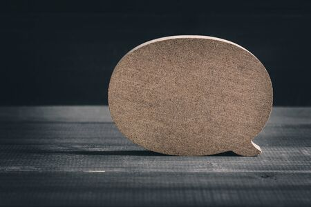 Wooden blank speech bubble on wood table background.