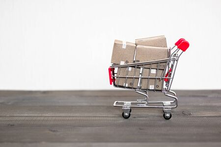 Shipping Box with shopping cart trolley on wood table Stock fotó