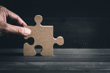 Hand hold wooden jigsaw puzzle on wood table background.