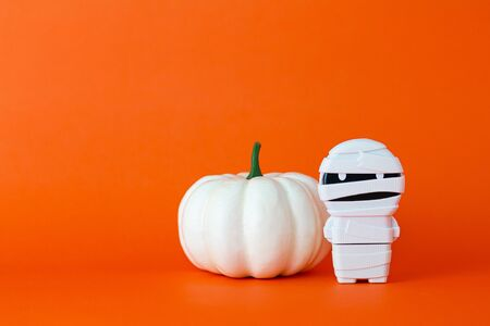 White pumpkin with mummy on orange background with copy space ,  halloween concept. Stock fotó