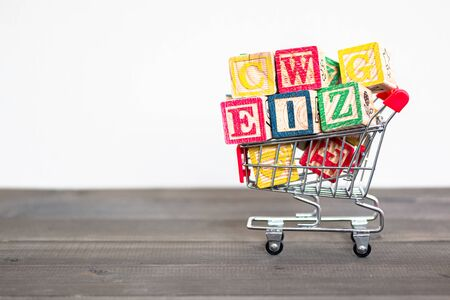 Wooden Alphabet Blocks with shopping cart trolley on wood table Stock fotó