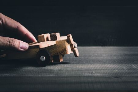 Hand hold wooden plane on wood table background. Education concept.