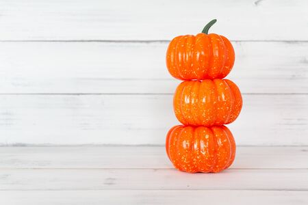 Stack of orange pumpkin on white wood table with copy space. Stock fotó