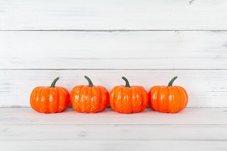 Orange pumpkin on white wood table with copy space.