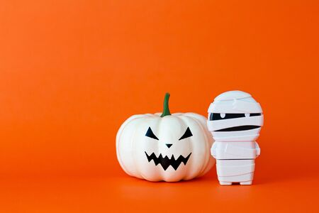 White ghost pumpkin with mummy on orange background with copy space ,  halloween concept.