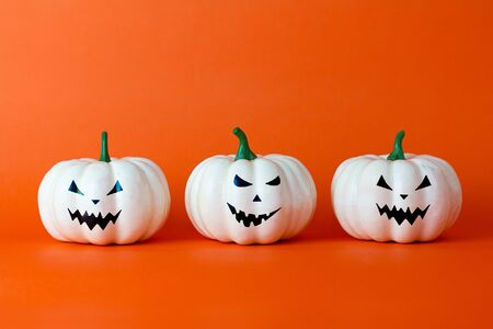 White ghost pumpkin on orange background with copy space ,  halloween concept.