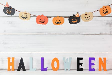 Halloween pumpkins decoration over white wood background and letters.
