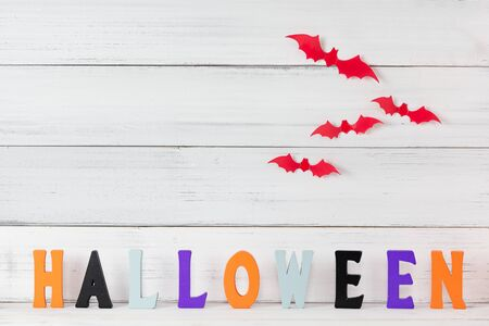 Halloween letters  and red bats flying over white wood background, decoration concept. Stock fotó