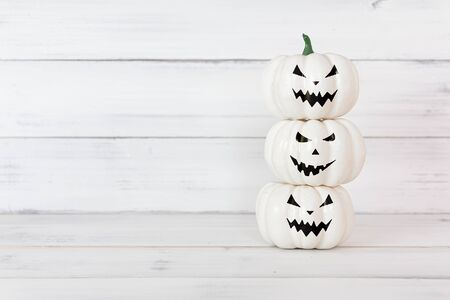 Stack of white ghost pumpkin on white wood table with copy space ,  halloween concept.