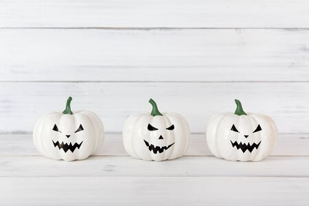 White ghost pumpkin on white wood table with copy space ,  halloween concept.