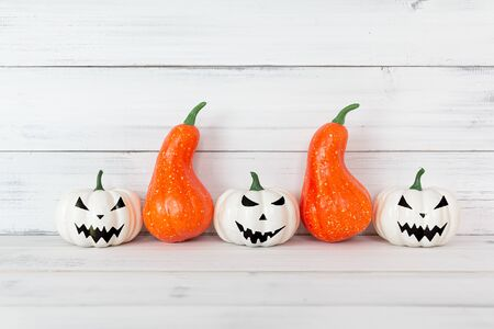 White ghost and Orange pumpkin on white wood table with copy space.