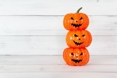 Stack of orange ghost pumpkin on white wood table with copy space ,  halloween concept.