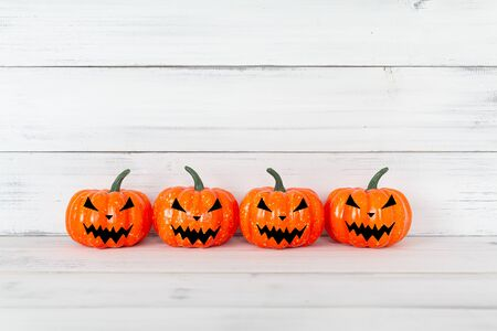 Orange ghost pumpkin on white wood table with copy space ,  halloween concept. Stock fotó