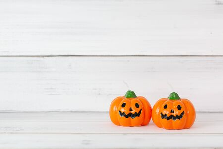 Orange candle pumpkin on white wooden background with copy space ,  halloween concept.