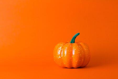 Orange pumpkin on orange background with copy space ,  halloween concept.