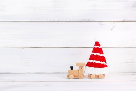 Christmas hat with wooden toy train on white wood background with copy space Stock Photo